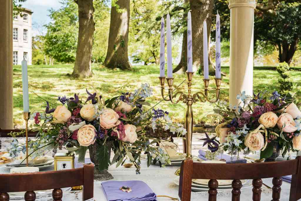 Handpainted wisteria on lilac candles for a Bridgerton themed afternoon tea table setting, sat in a gold candelabra