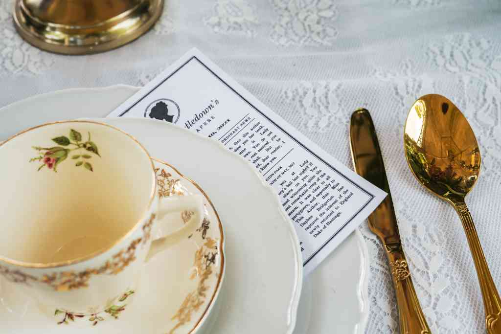 Gold vintage tea cup and saucer on a lace tablecloth with gold cutlery