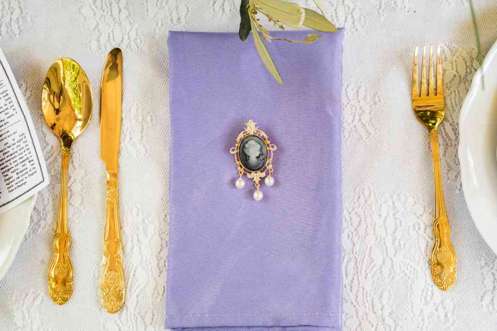 Gold cutlery with a lilac fabric napkin with a faux pearl cameo brooch attached
